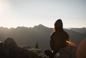 Achtsamkeitsmeditation Frau sitzt bequem auf Stein und schaut in die Ferne
